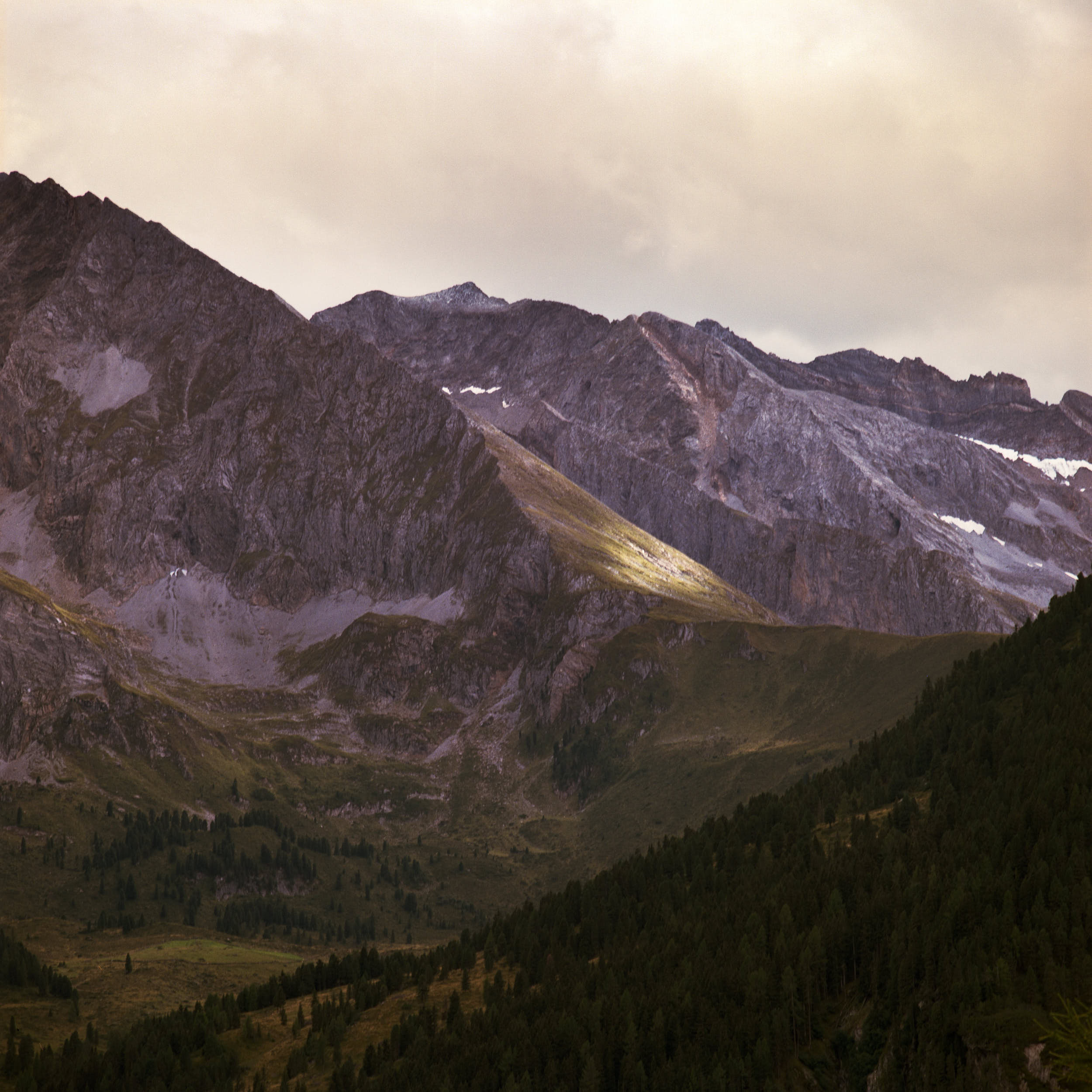 Film landscape photography: beautiful alpine peaks with spots of sunlight.