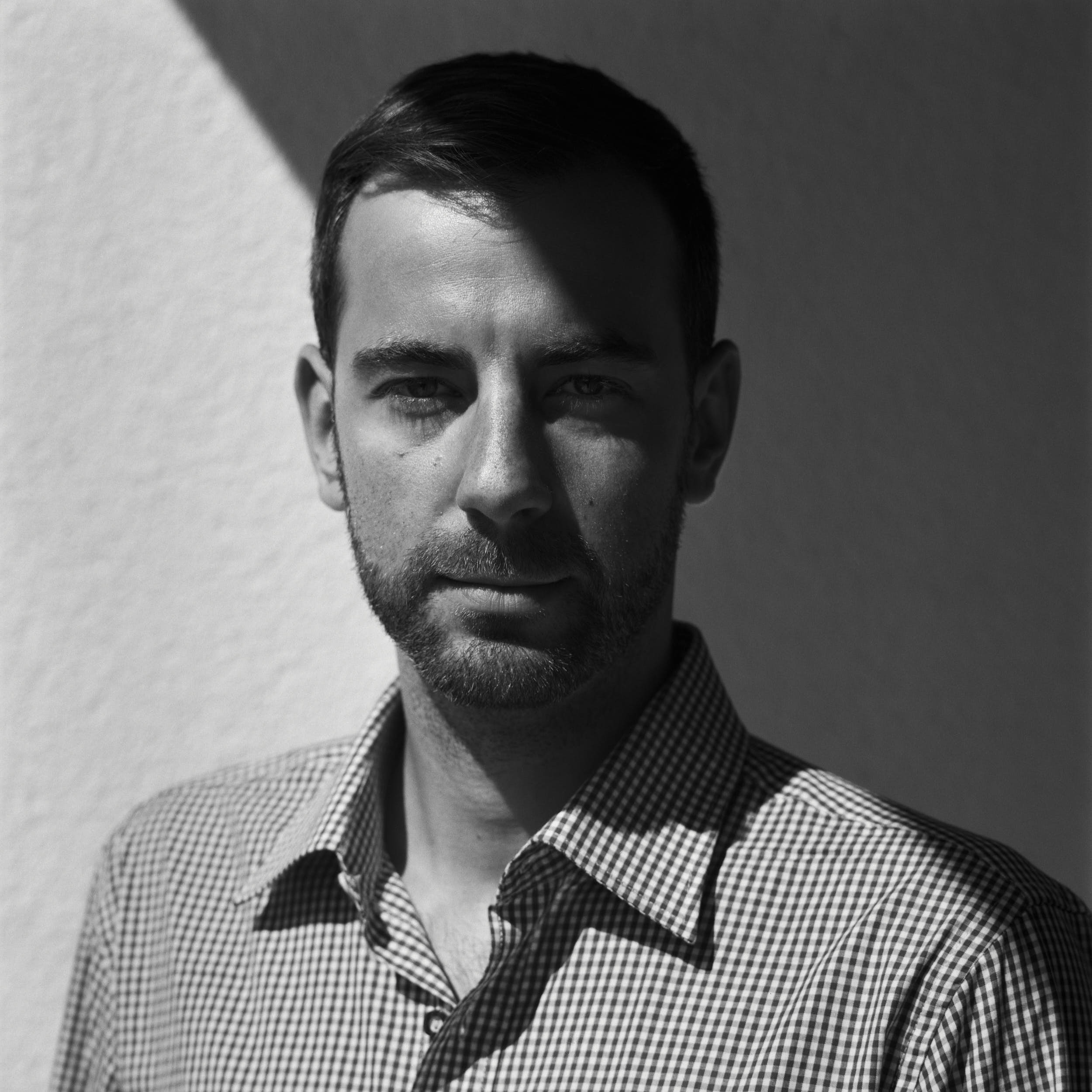 Contrasty portrait of a man with deep shadows wearing checkered shirt. Medium format film photography.