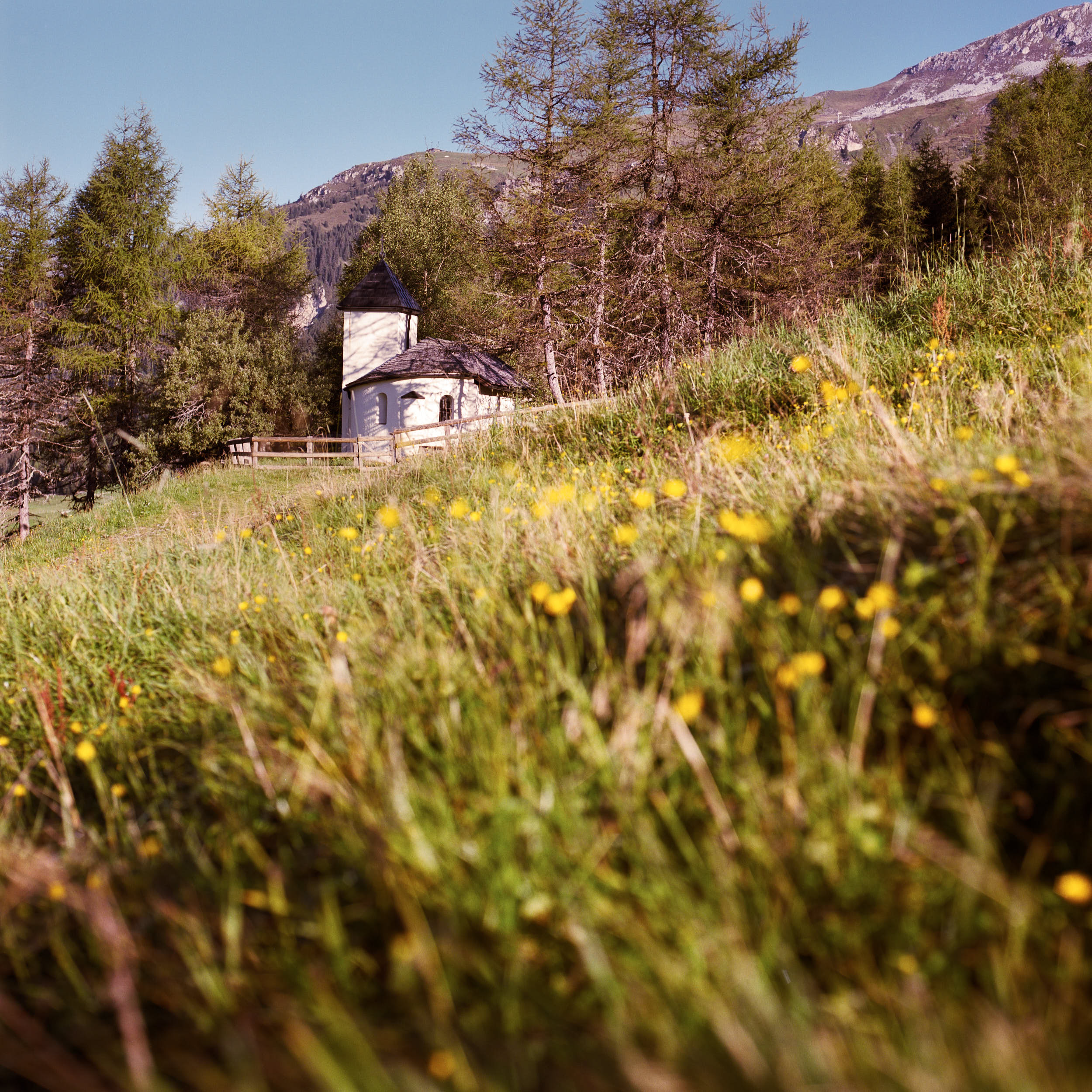 Mountain landscape photography: small mountain chapel on an alpine meadow.