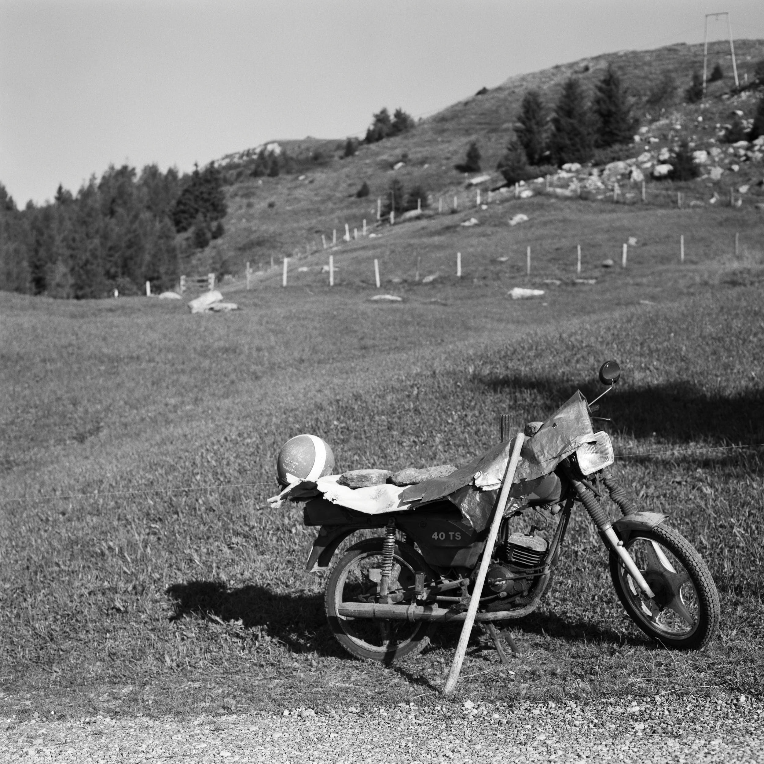 Black and white documentary photography: motorcycle parked on the side of a mountain road.