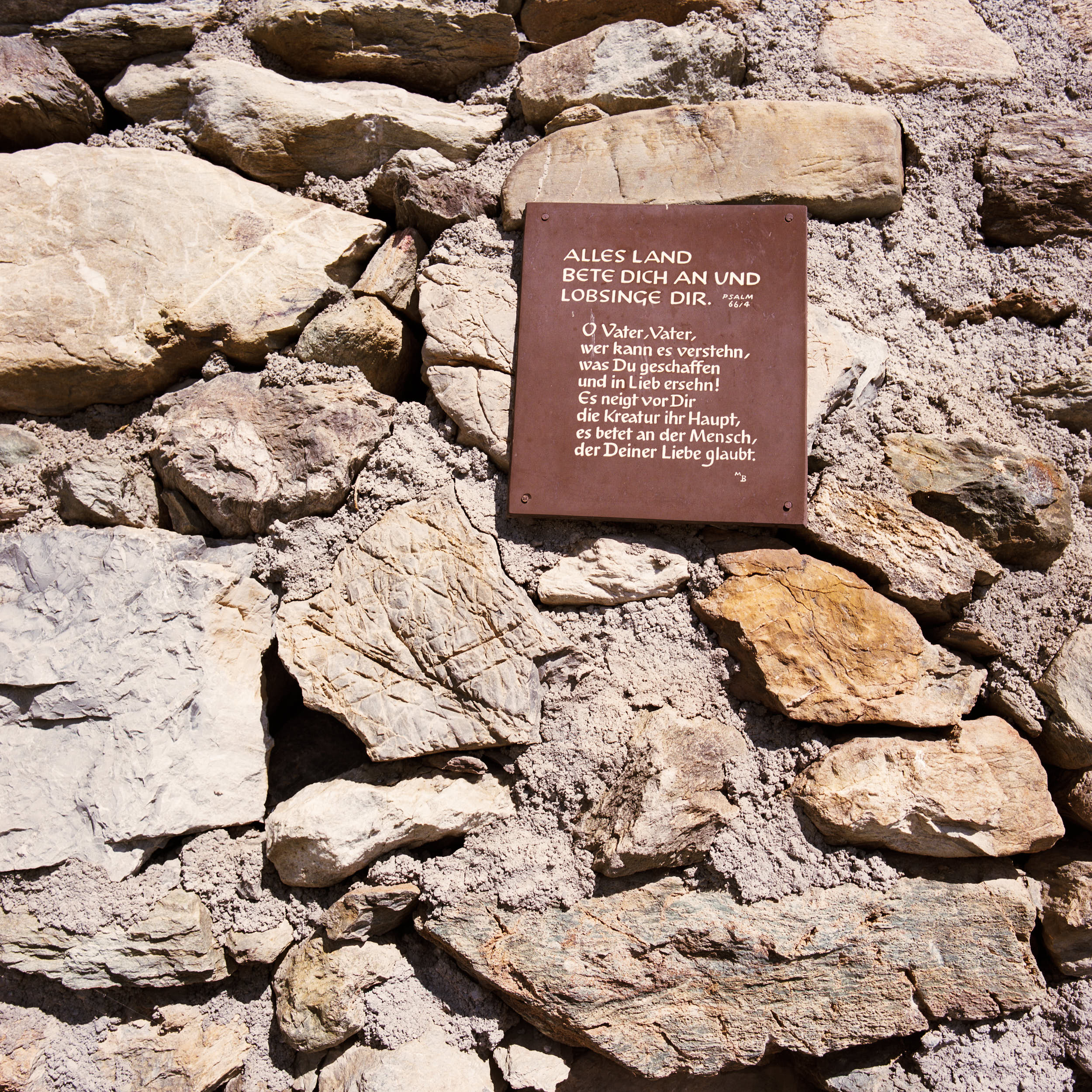 Medium format documentary photography: religious signpost attached to a rock in an austrian alpine village.