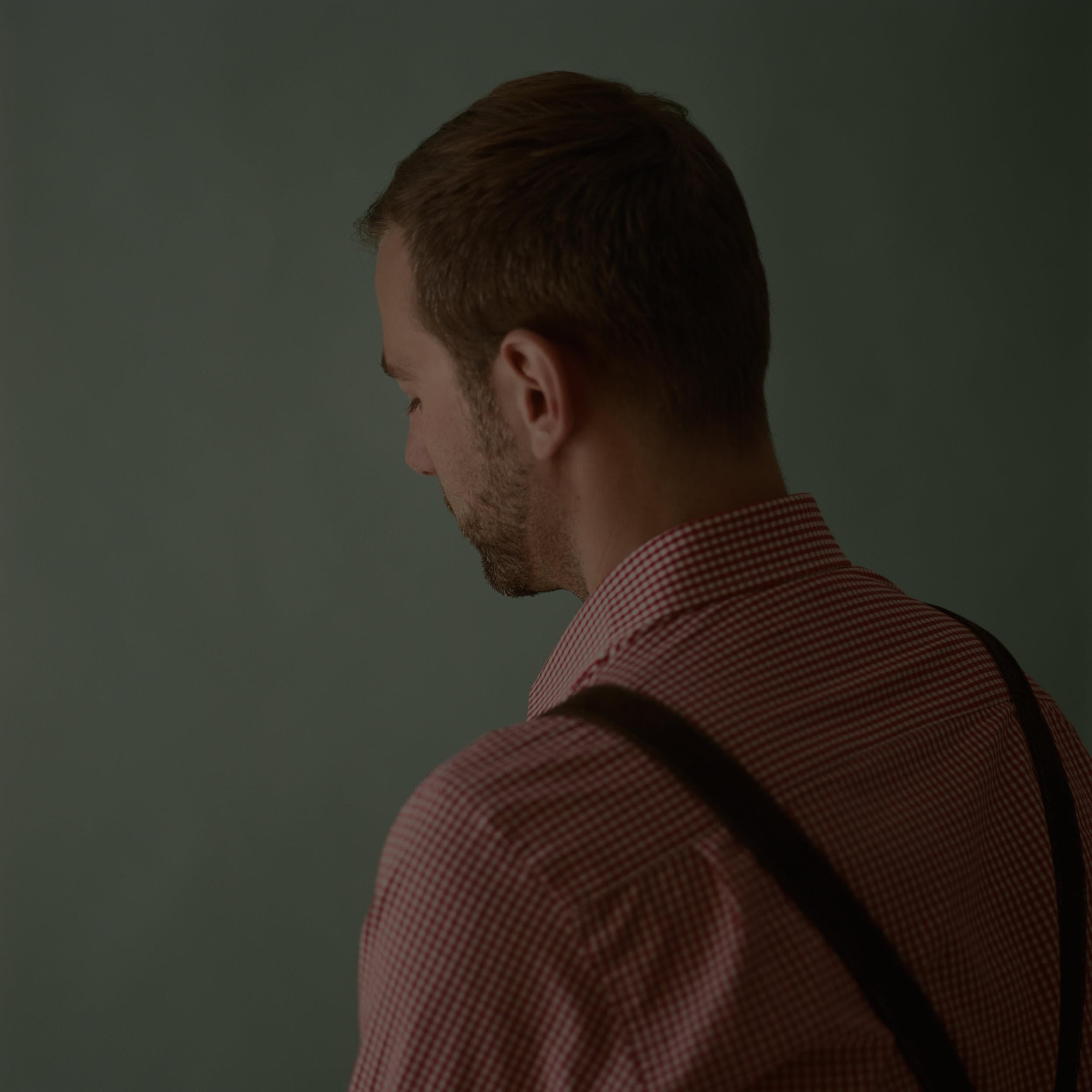 Moody medium format portrait of an austrian man in a traditional wardrobe.