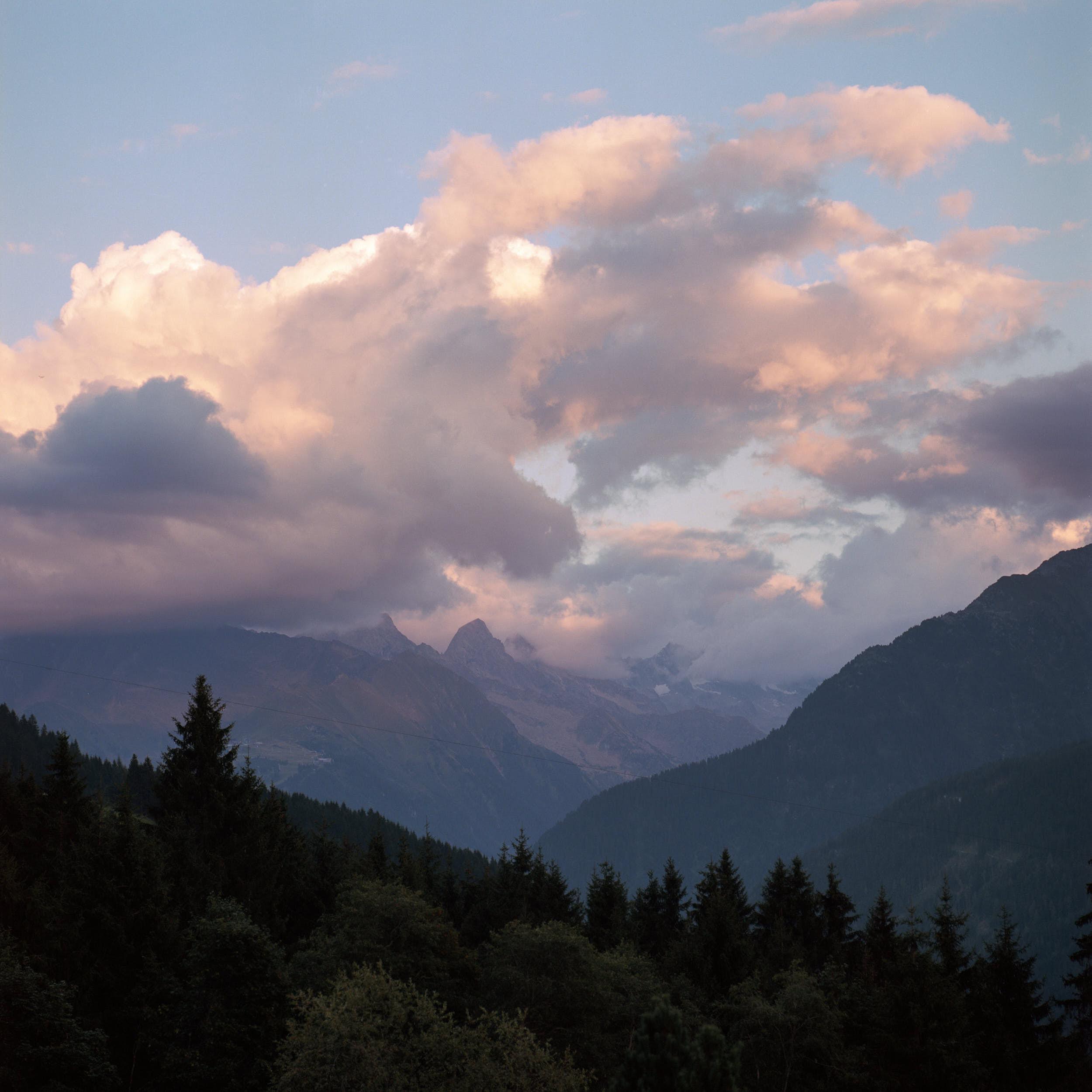 Last sun hitting high alpine peaks with dramatic sky.