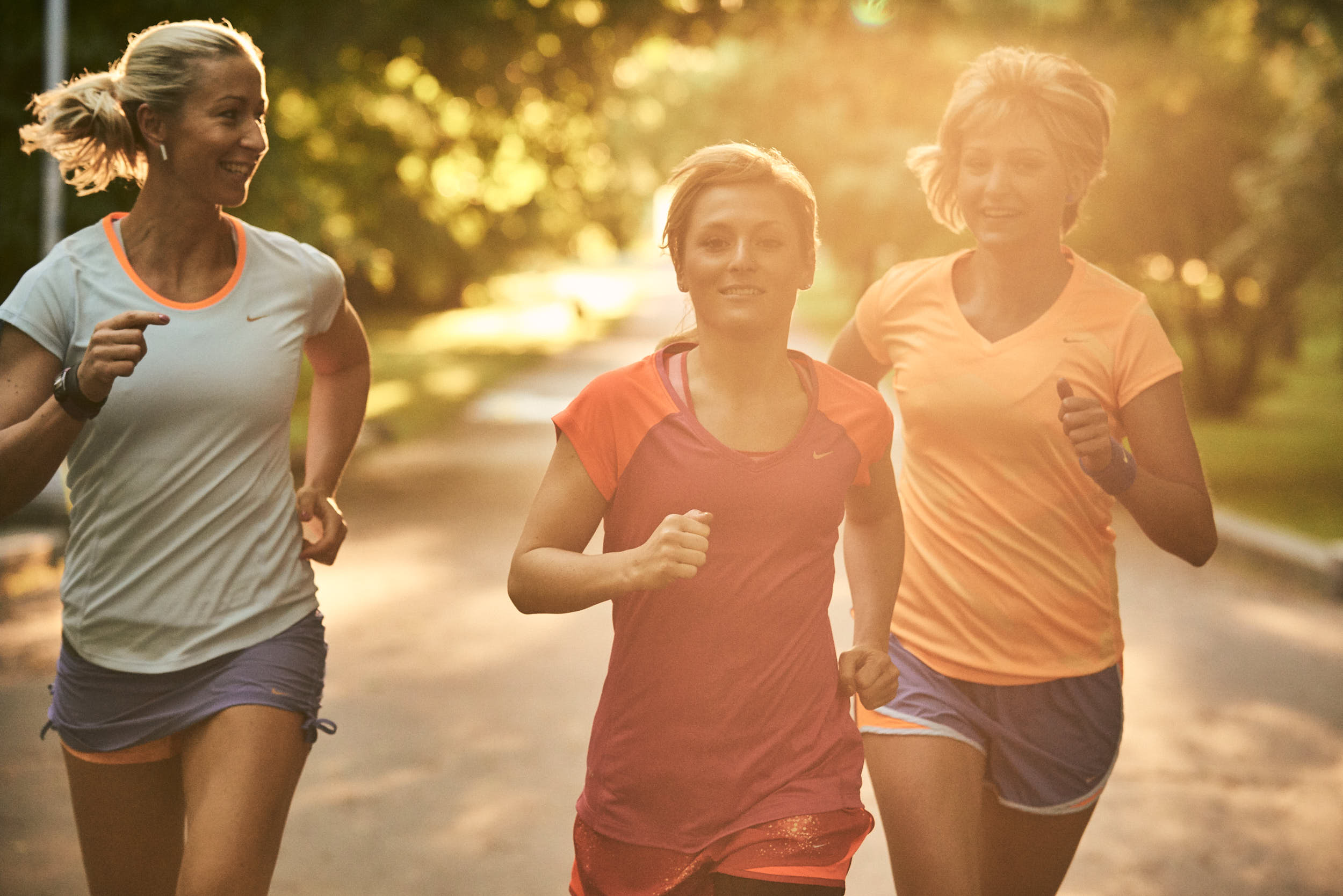 Group of girls running in a park with sunflare coming through the leaves.