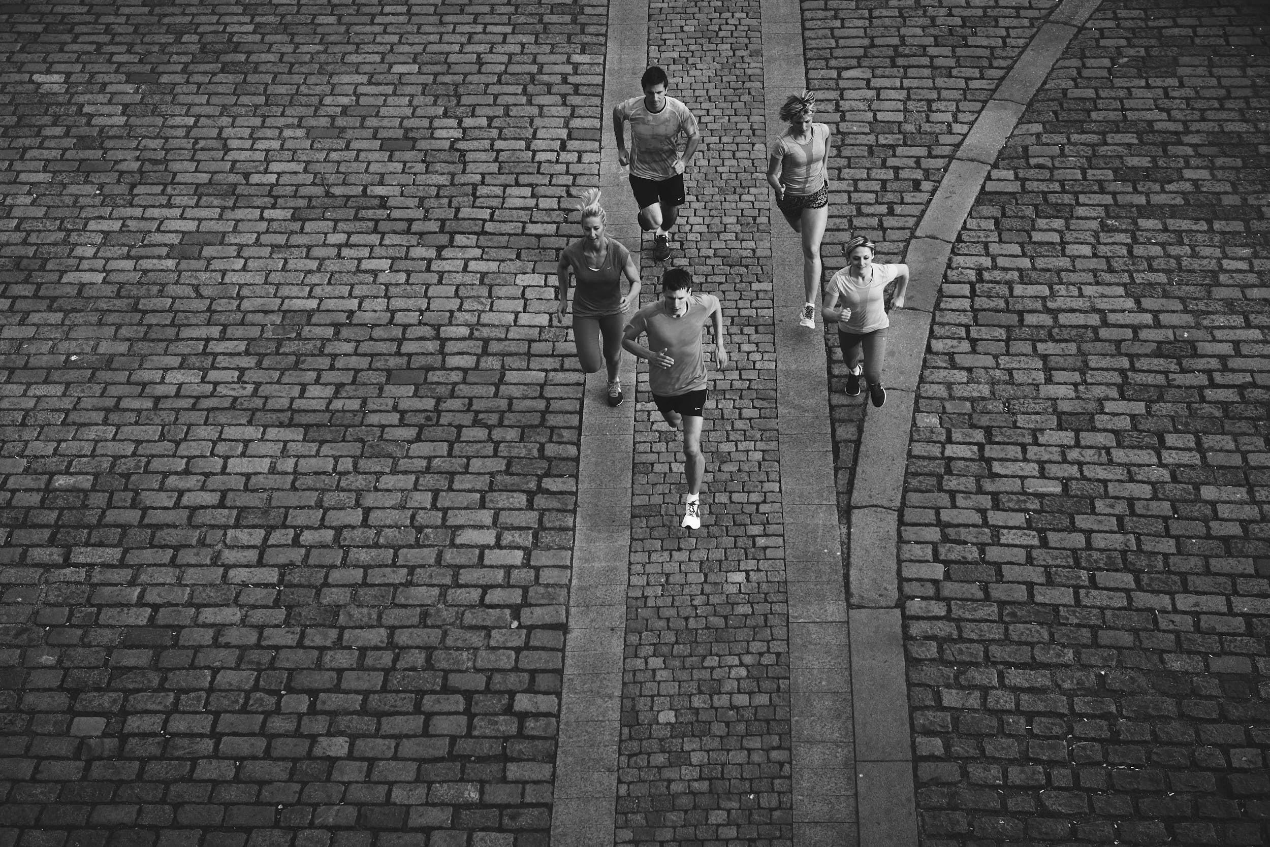 Black and white sports photography: group of runners on pavement photographed from elevated perspective.