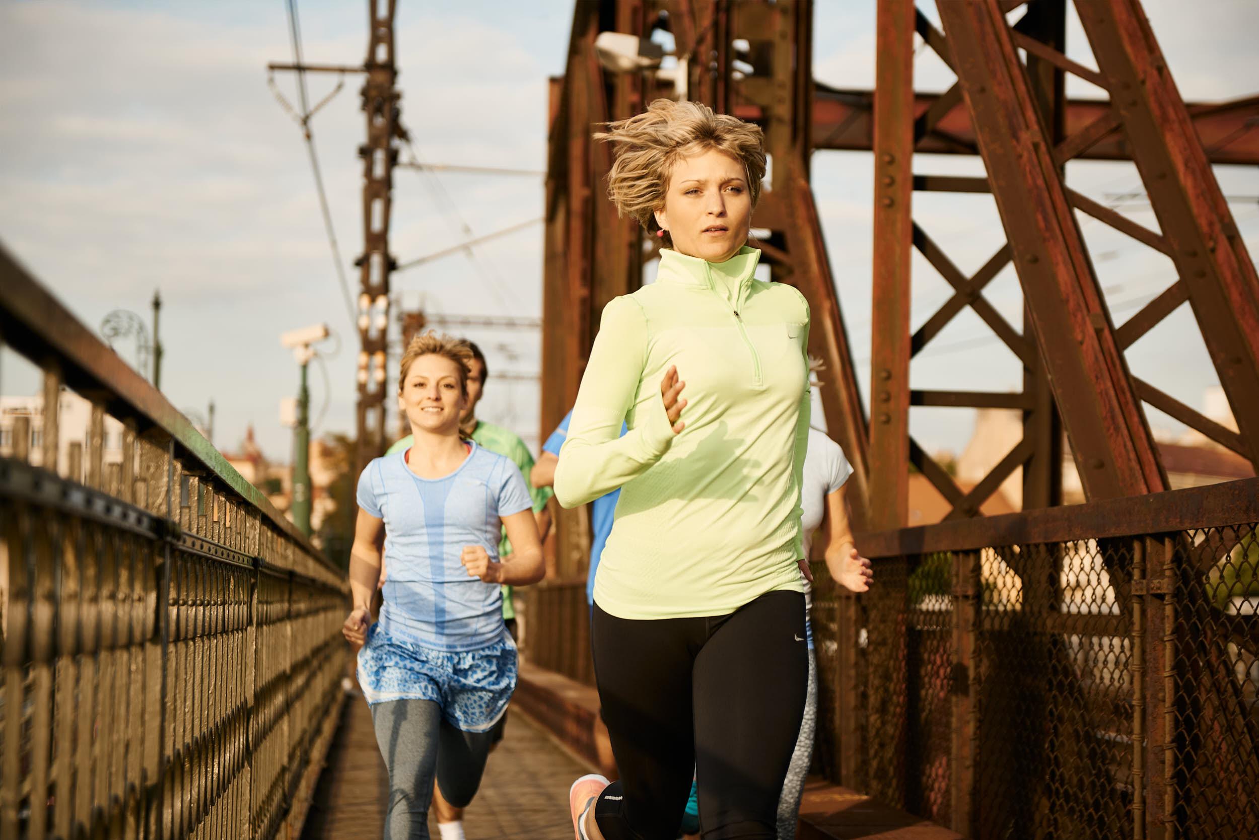 Group of runners on a railway bridge.