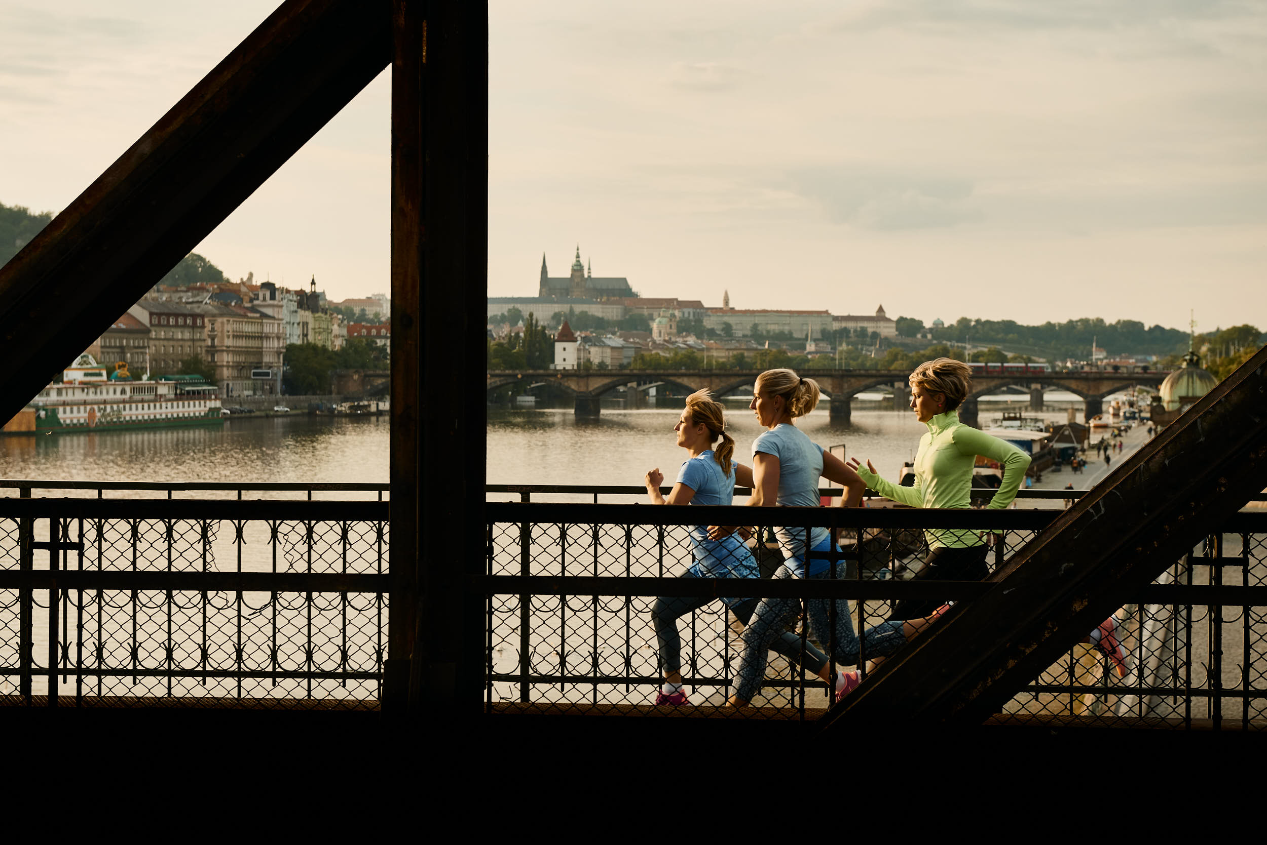 Group of women running across a railway bridge with Prague Castle in the background. Sport apparel advertising campaign.