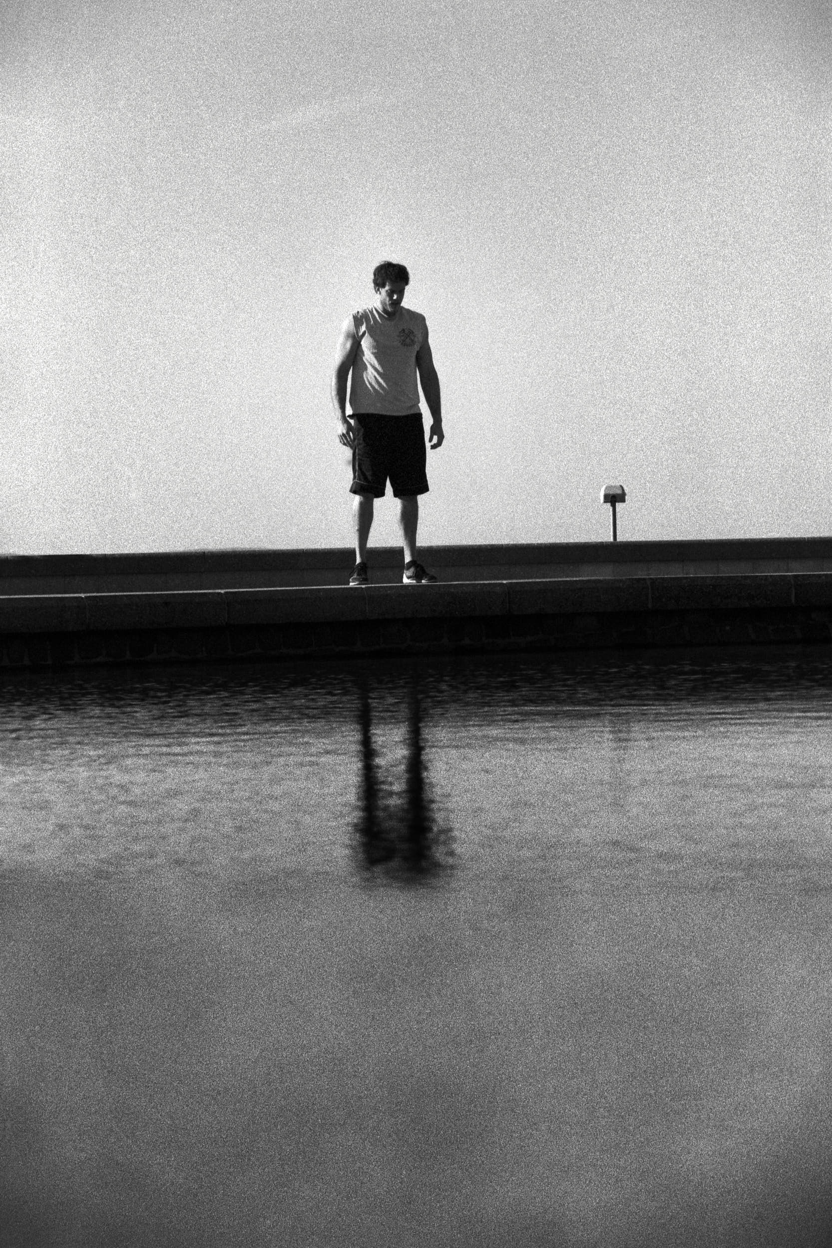 Fitness athlete standing on a curb. His body is reflected on a water surface beneath.