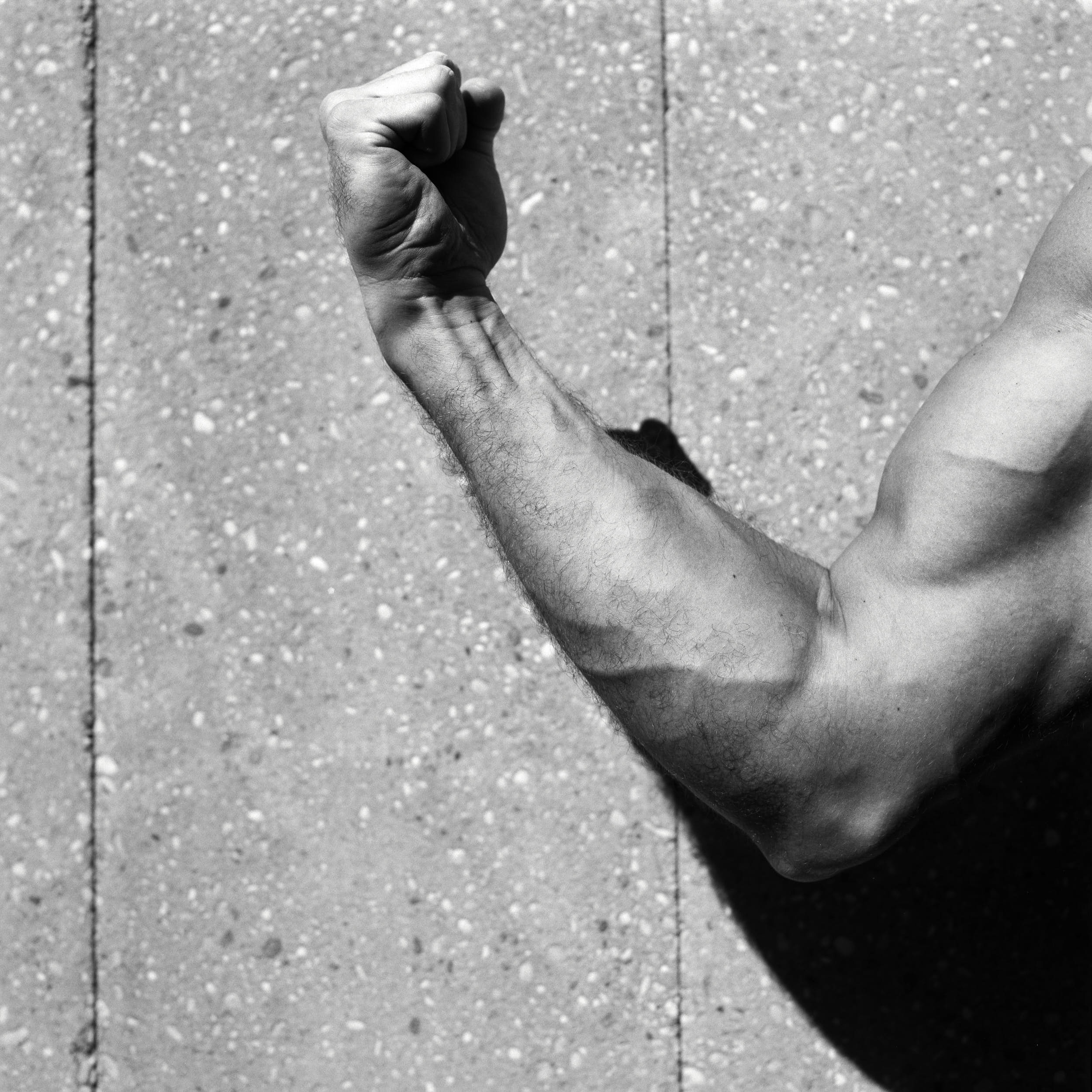 Black and white close up of a flexed biceps in front of a concrete wall.