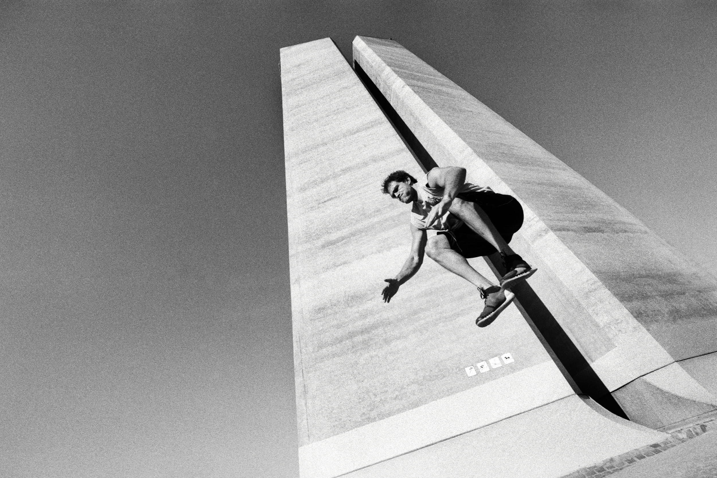 Fitness advertising photography: athlete jumping up with concrete brutalist structure in the background.