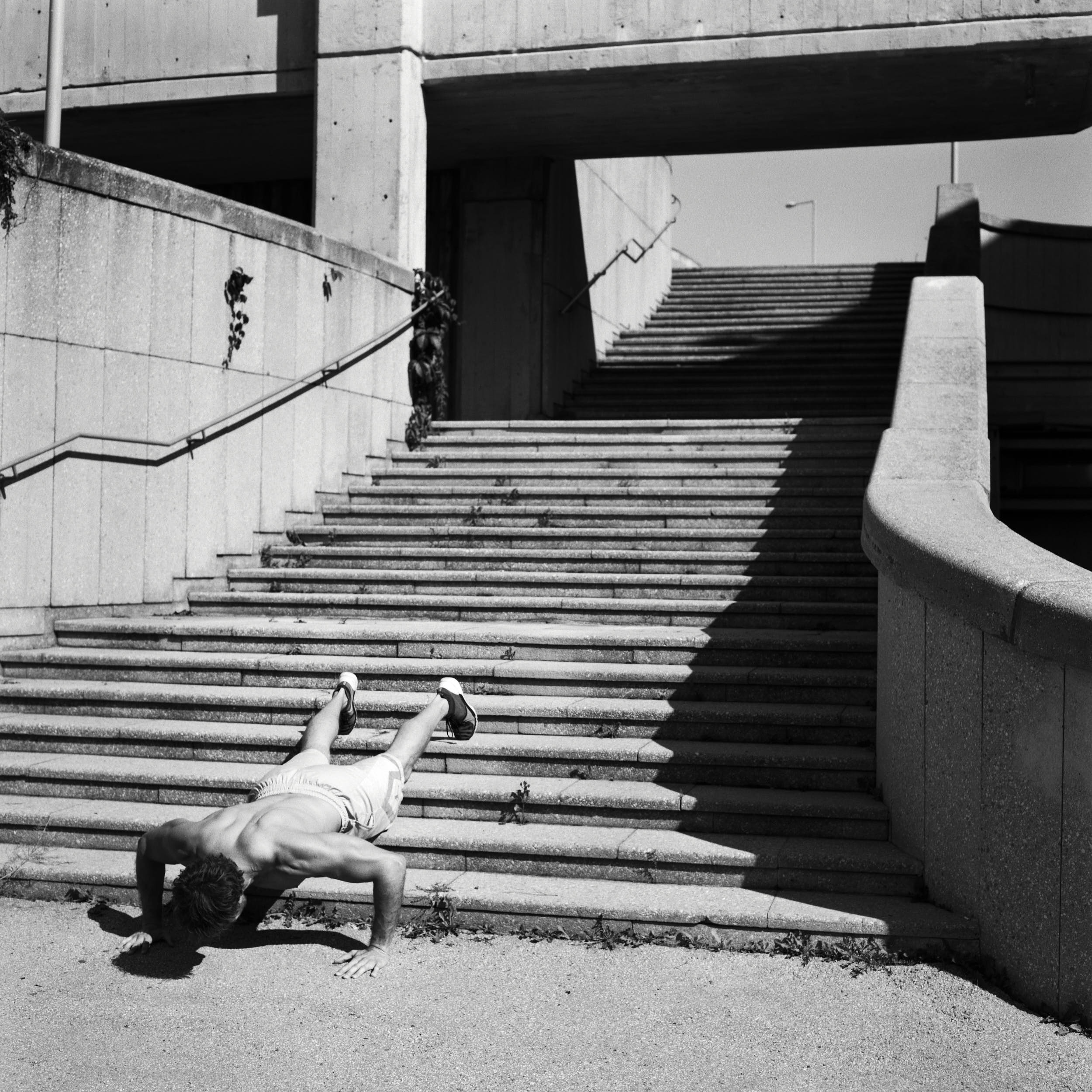 Crossfit athlete doing push ups on a concrete staircase.