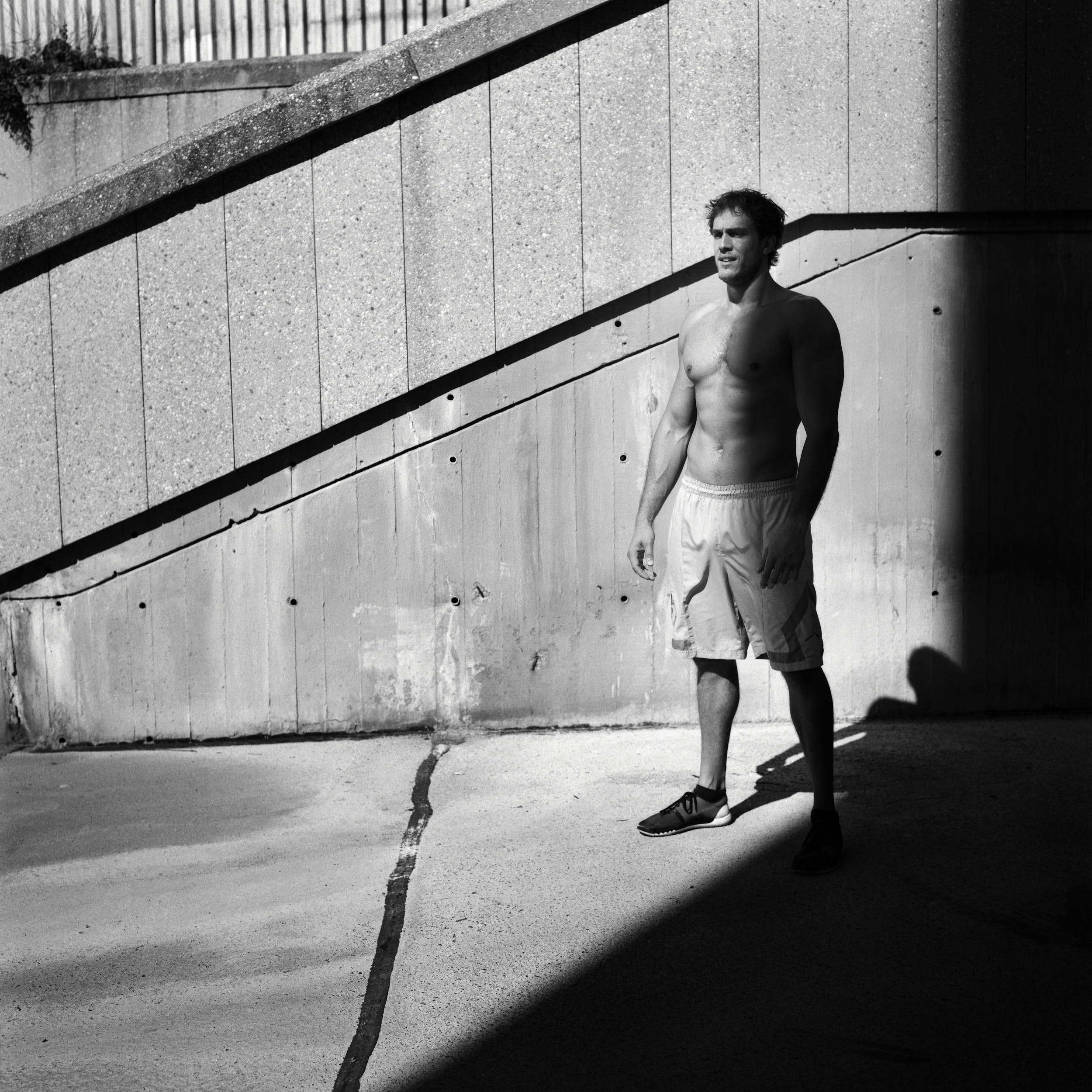 Active lifestyle photography: muscular athlete standing in the shadow.