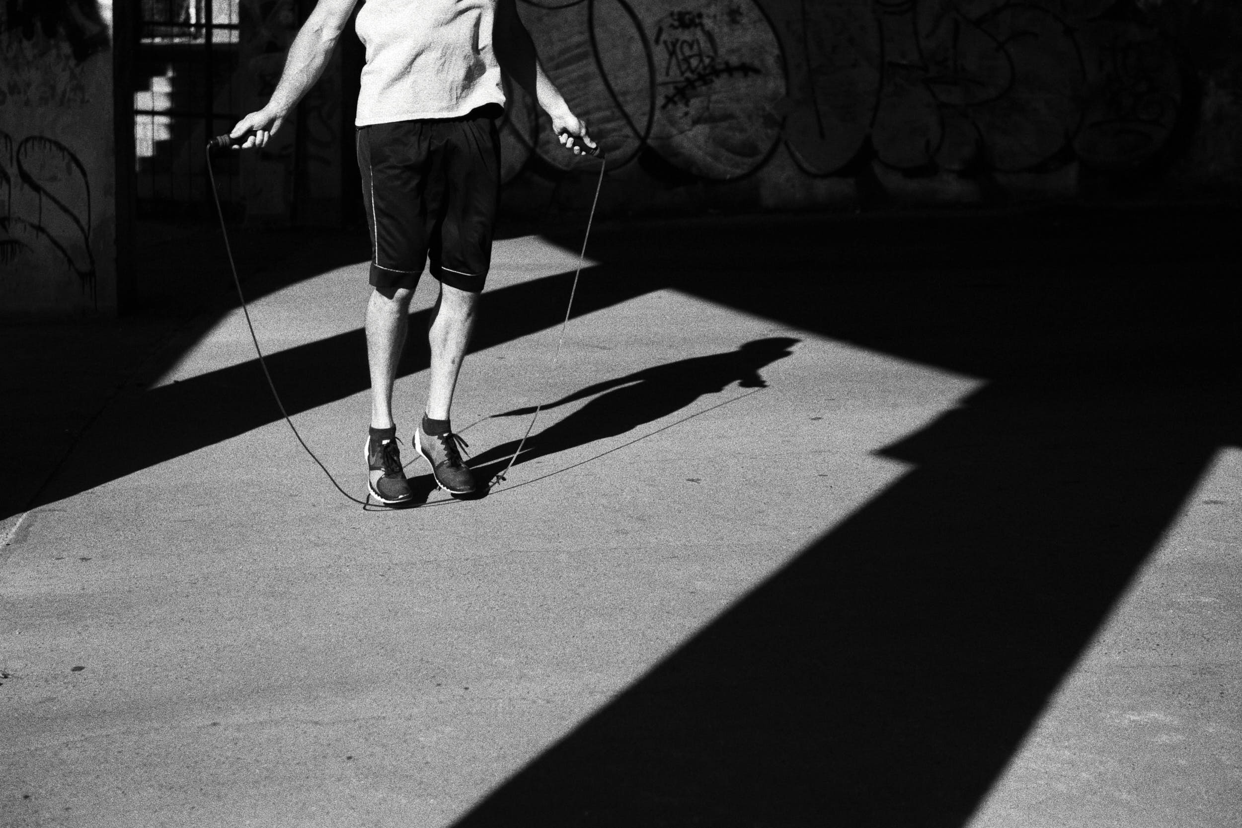 High contrast detail of a man working out with a jump rope.