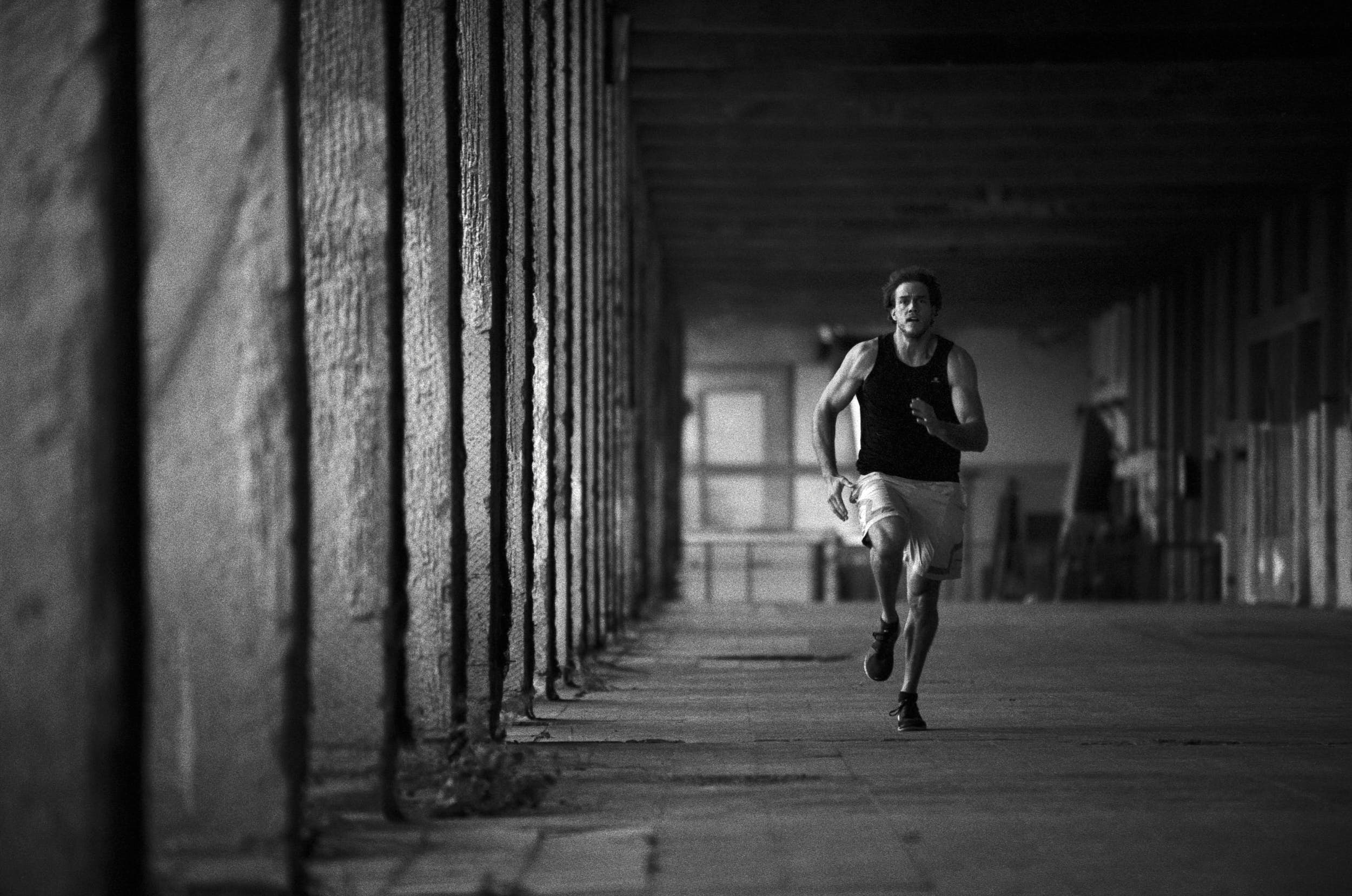 Muscular athlete sprinting in an industrial warehouse.