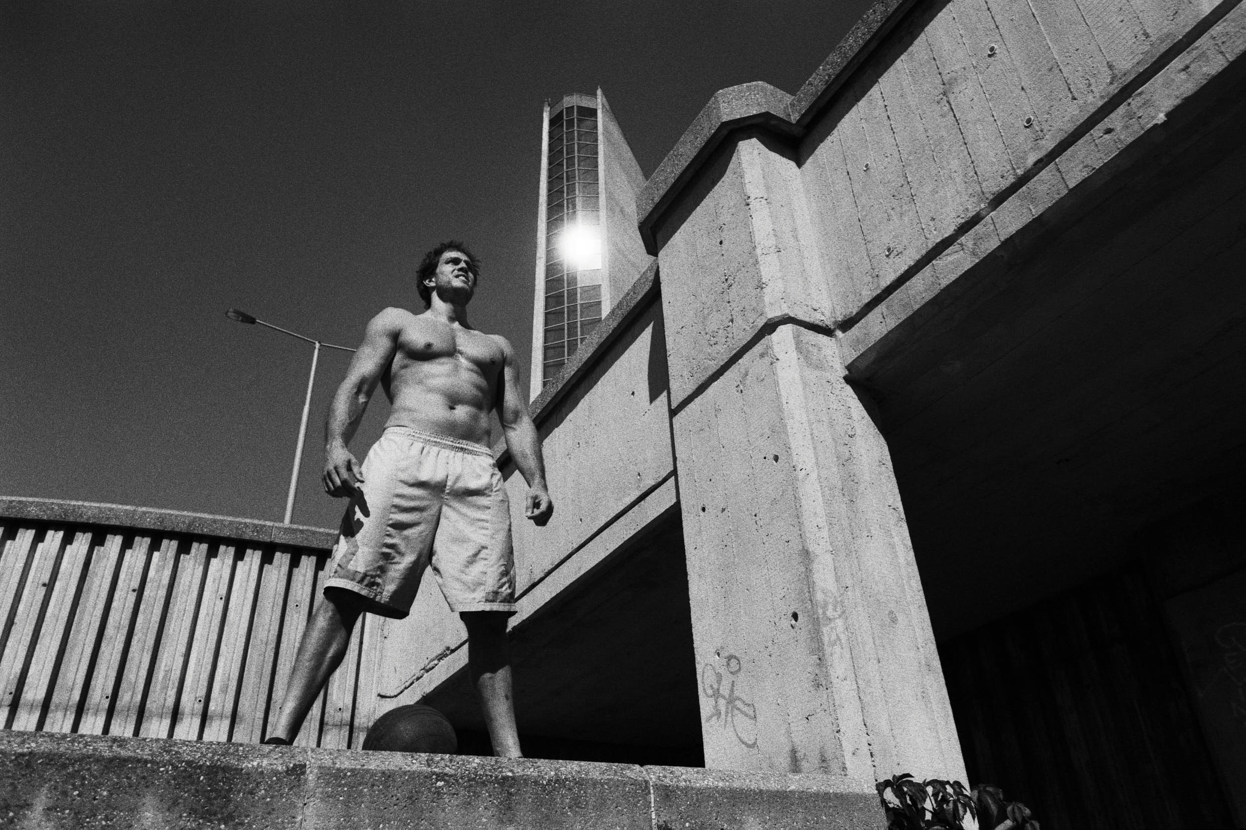 Crossfit athlete on a brutalist staircase preparing for a work out with a medicine ball.