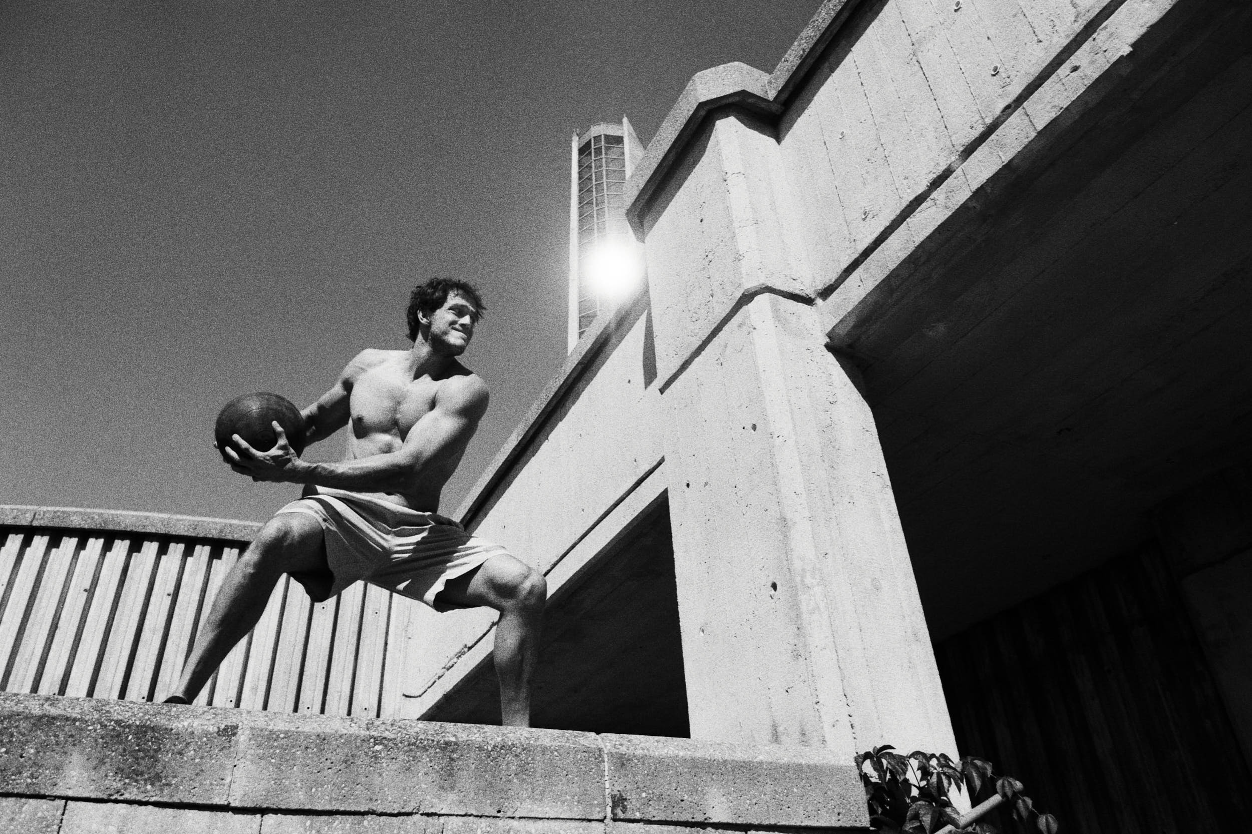 Action sports photography: Crossfit athlete on a brutalist staircase preparing for a work out with a medicine ball.