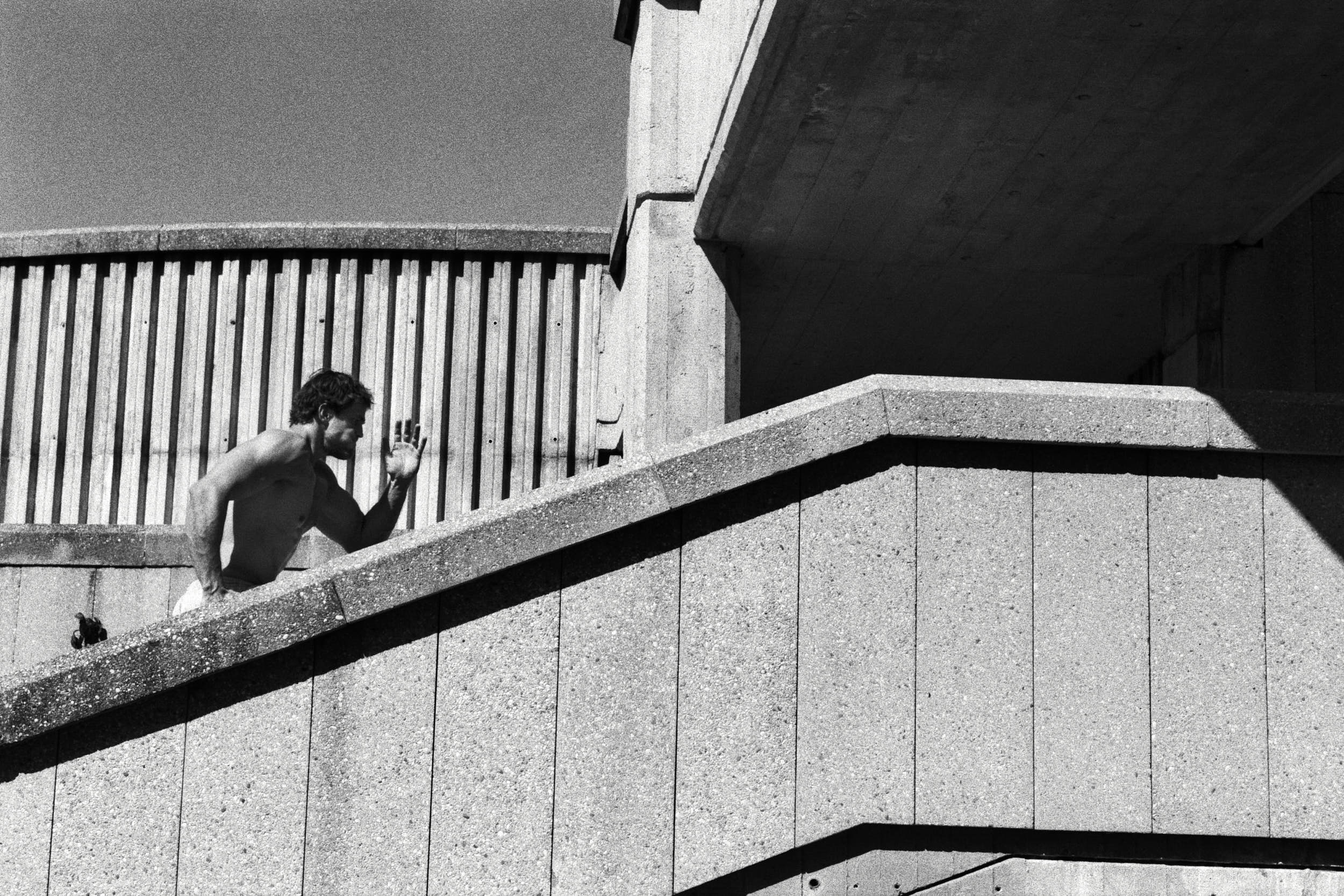 Athlete running up a concrete brutalist staircase.