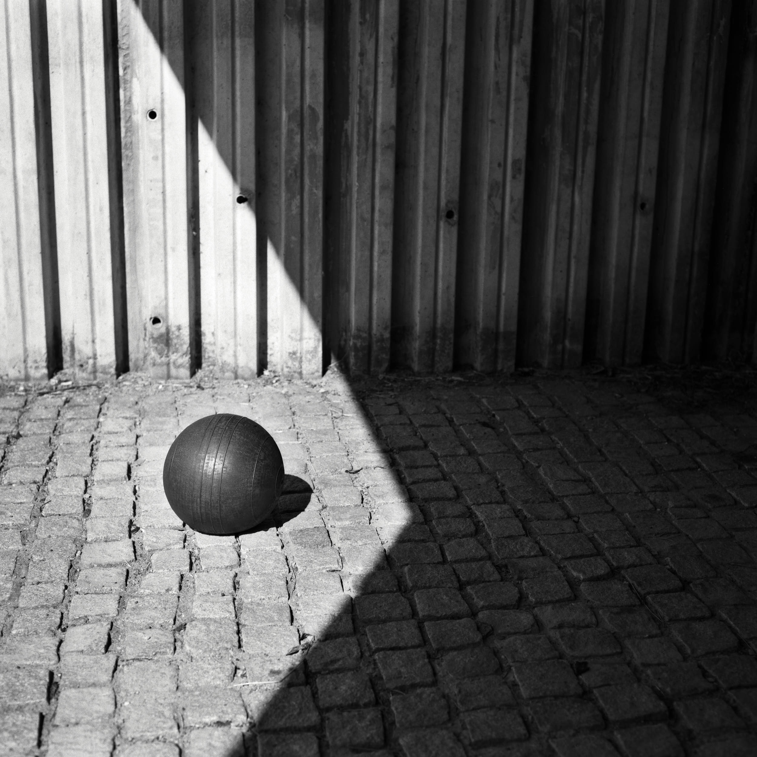 Sports still life photography: medicine ball in a geometric composition with deep shadows and high contrast.